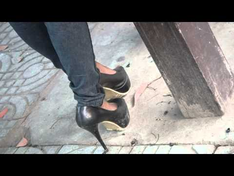 The lady play her shoes when waiting for bus